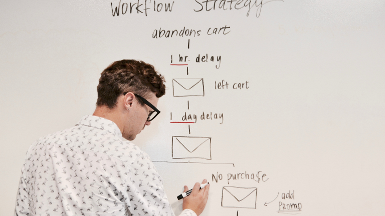 man drawing email automation series on a board